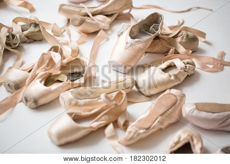 Many pairs of ballet shoes lie in a chaotic order on the floor. Pointe in a different state from new to severely trampled. Horizontal.