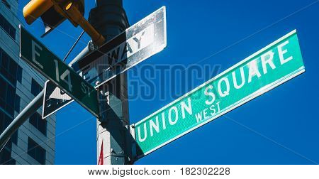 Street sign of Union Square and East 14 St with skylines in background.- New York USA