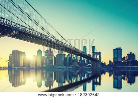 View of Brooklyn Bridge and Manhattan skyline WTC Freedom Tower from Dumbo at sunset Brooklyn. Brooklyn Bridge is one of the oldest suspension bridges.