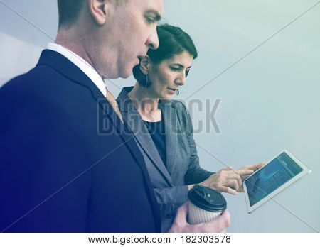 Business people analysing on digital tablet with partner