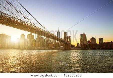 View of Brooklyn Bridge and Manhattan skyline WTC Freedom Tower from Dumbo at sunset Brooklyn. Brooklyn Bridge is one of the oldest suspension bridges in the USA