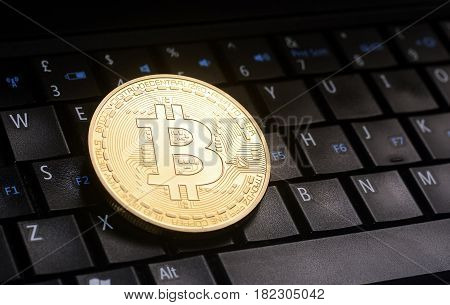 Golden bitcoin coin placed  on laptop keyboard