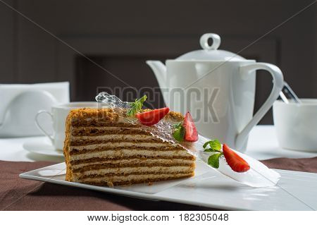 piece of honey cake on a white plate , decorated with strawberries