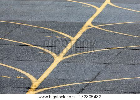 Airport taxiway yellow lines near airport runway