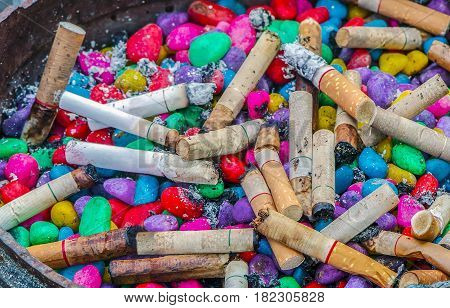 Lots of cigarette buds in a large ash tray with colorful stone