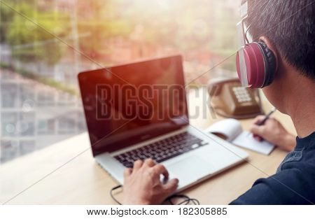 young man working at the office using headset and laptopwith the sunlight in morning