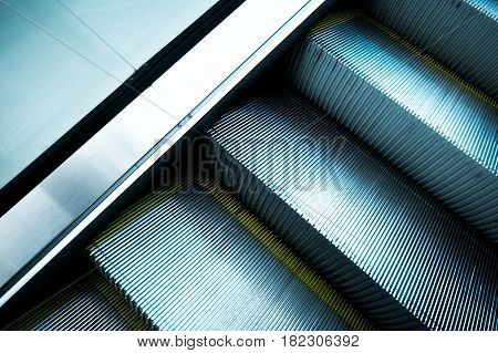 Abstract escalator in international airport with yellow bands and metal line steel