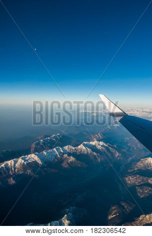 Looking through the window aircraft during flight a snow covered Italian and Osterreich Alps with blue sky without clouds.