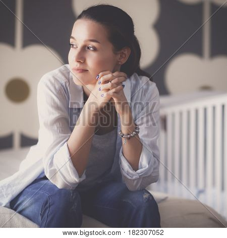 Young woman sitting on the bed near childrens cot