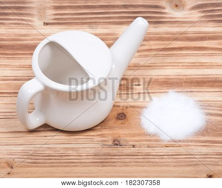 Ceramic neti pot and saline on wooden vintage background