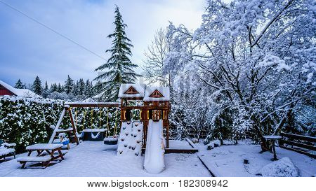 Snow covered Play Ground in the Fraser Valley of British Columbia, Canada on a cold winter day and with snow covered trees and lawn