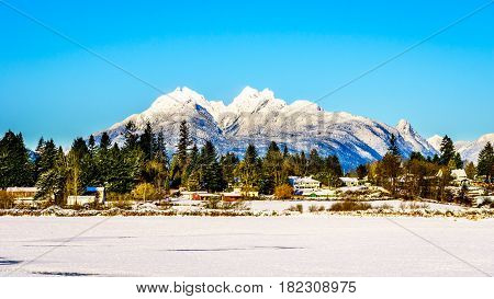 The snow covered peaks of the Golden Ears mountain and Mount Robie Reid behind the town of Fort Langley in the Fraser Valley of British Columbia, Canada on a cold winter day and snow covered fields