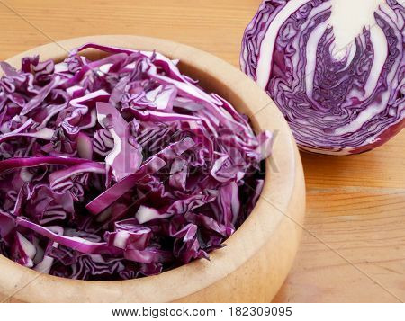 Shredded red cabbage in wooden bowl. Vegetarian healthy food.