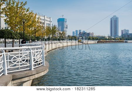 Tianjin, China - Nov 1, 2016: Shoreline along the Haihe River as viewed from Tianjin Railway Station. Image features a modern public walkway with railings.