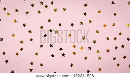Golden Star Sprinkles On Pink. Festive Holiday Background. Celebration Concept
