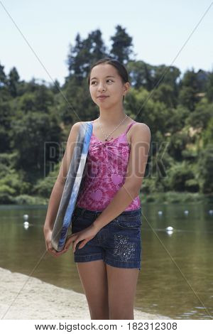 Mixed race girl holding boogie board near lake