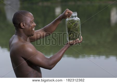 African man holding insect jar
