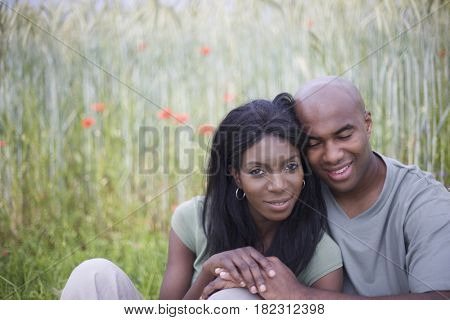 African couple sitting in field of flowers