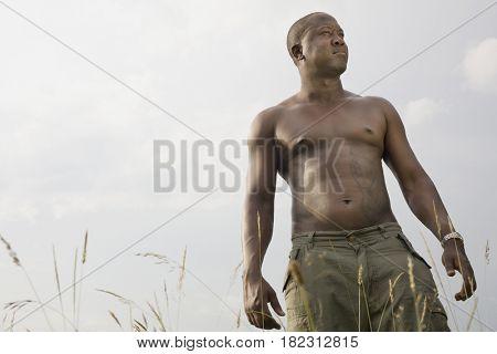 Shirtless African man outdoors