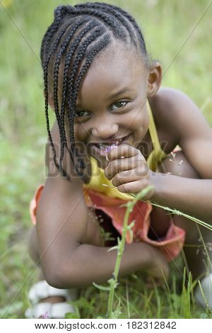African girl playing with grass
