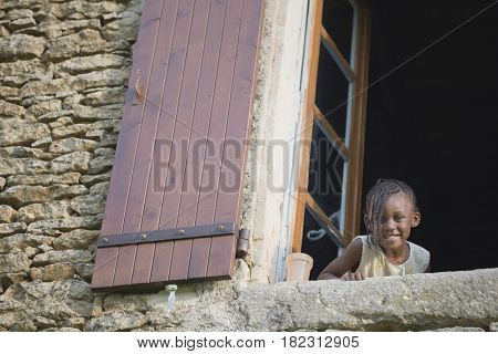 African girl peering out window