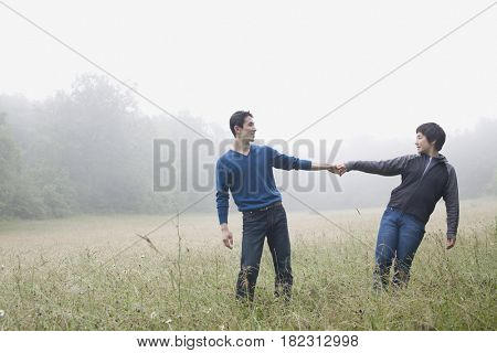 Asian couple holding hands in remote field