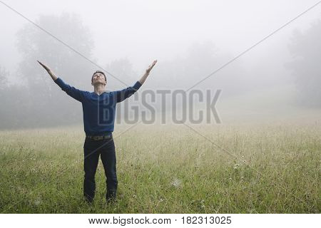 Asian man with arms outstretched in remote field