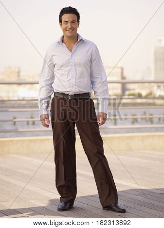 Confident man standing on boardwalk at waterfront