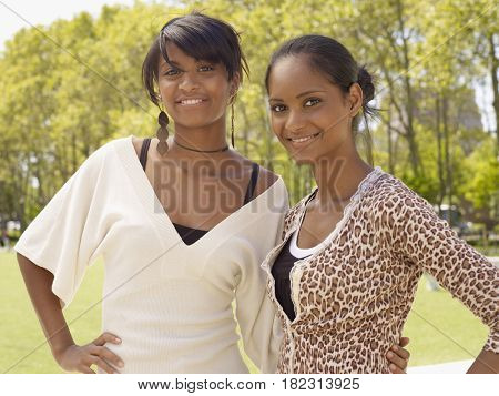 Women standing in park wearing trendy fashions