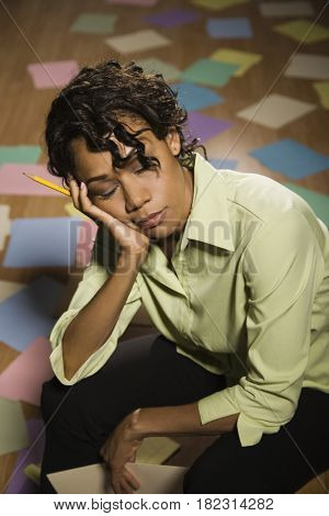 Frustrated mixed race businesswoman sitting in mess