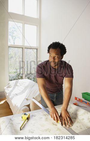 African man measuring wallpaper