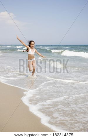 Hispanic girl running in waves at beach