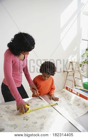 African mother teaching son to measure wallpaper