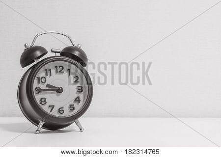 Closeup alarm clock for decorate show a quarter to ten o'clock or 9:45 a.m. on white wood desk and cream wallpaper textured background in black and white tone with copy space