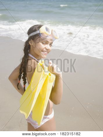 Hispanic girl carrying flippers and goggles