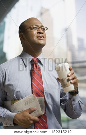 African businessman holding coffee and newspaper