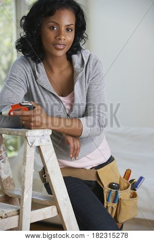 African woman with drill and toolbelt