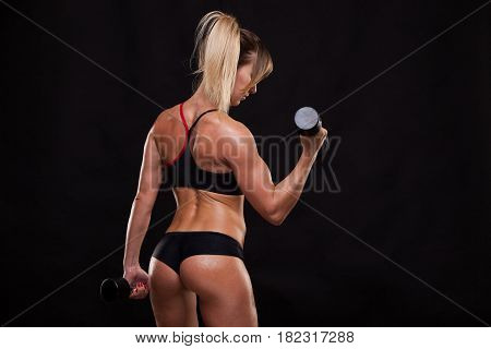 Attractive athletic woman is pumping up muscles with dumbbells, back view isolated on dark background with copyspace.