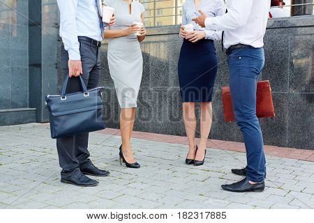Low section shot, group of business people talking outside modern office building