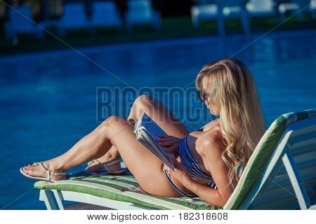 Girl is sunbathing and reading a book by the swimming pool. She is wearing a beautiful swimsuit and pretty suglasses.