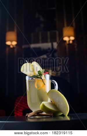 Glass of delicious glintwein or mulled hot wine on cutting board with cinnamon, thread, anise, pear, honey, wooden spoon and silver star on vintage wooden background