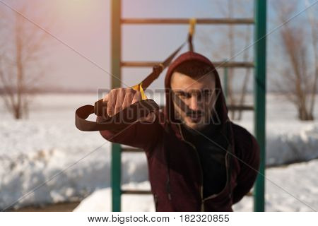 Male sporty adult exercising with fitness straps outdoors. Young caucasian or middle eastern man in sportswear workoing out. winter workout