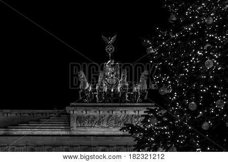 A fragment of the Brandenburg Gate (Quadriga close-up) and a fragment of a Christmas tree in the foreground. Black and white.