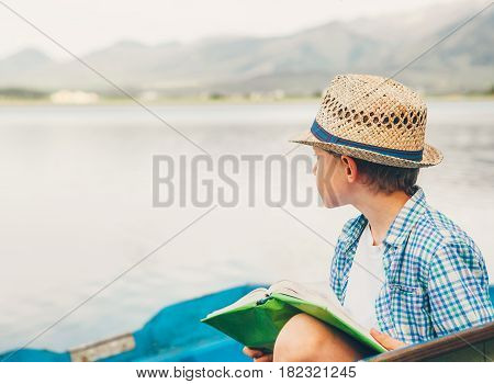 Boy lost in mind sits in the old boat with book