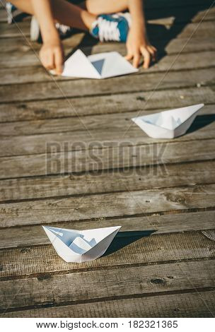 Child makes a paper boats sitting on wooden pier