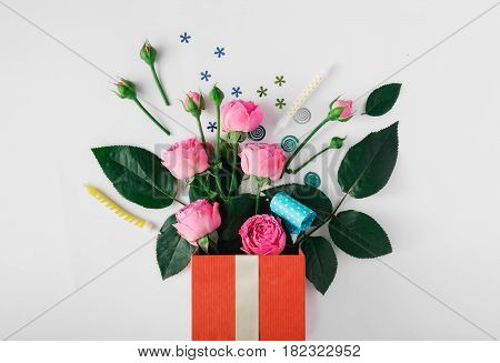 Red gift box with roses party confetti streamers noise makers and candles on a white background. Colorful celebration background. Flat lay. Top view