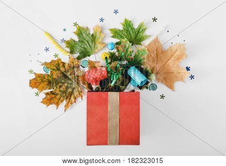Red gift box with various colorful dry leaves party confetti streamers noise makers and candles on a white background. Colorful celebration background. Flat lay