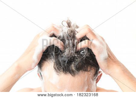 Closeup young man washing hair with white background health care concept