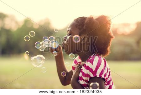 Kid with bubbles in a park