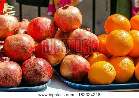 Fruits of pomegranates and oranges are sold on the street. Close-up.